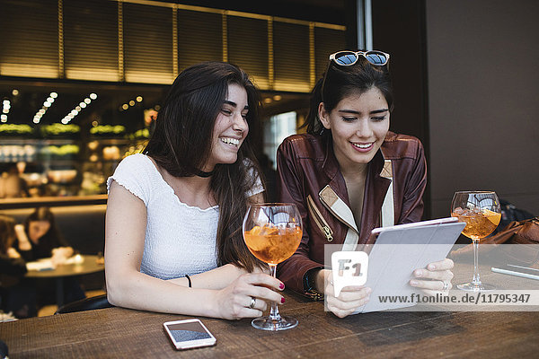 Two happy young women looking at tablet in a bar