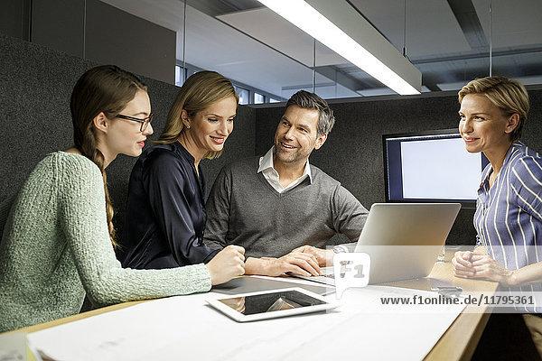Kollegen mit Laptop,  die eine Besprechung in der Besprechungsbox haben