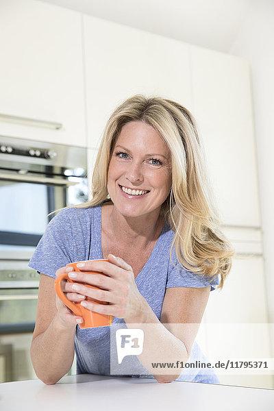 Porträt der lächelnden Frau zu Hause bei einer Tasse Kaffee