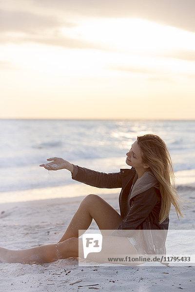 Junge Frau genießt den Strand bei Sonnenuntergang