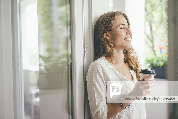 Lächelnde junge Frau mit Kaffee zum Mitnehmen am Fenster
