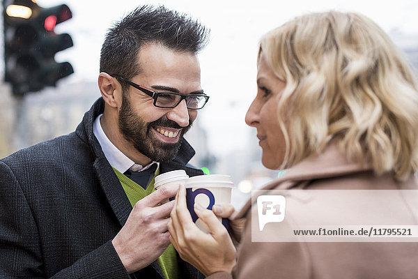Lächelnder Geschäftsmann und Geschäftsfrau mit Kaffee zum Mitnehmen in der Stadt