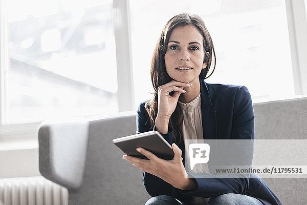 Porträt einer selbstbewussten Geschäftsfrau mit Tablette auf der Couch