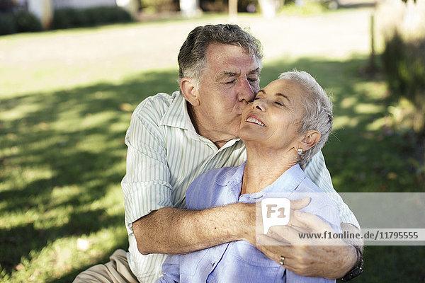 Senior Mann küsst seine Frau im Garten