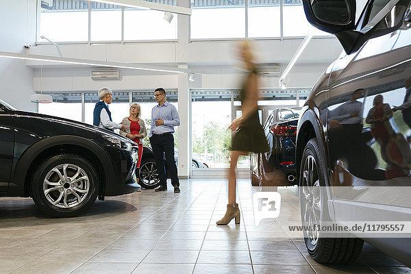 Autohaus berät Kunden mit Frau im Vordergrund
