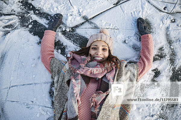 Porträt einer glücklichen Frau,  die auf dem gefrorenen See liegt.