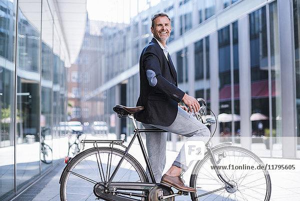Lächelnder Geschäftsmann auf dem Fahrrad in der Stadt