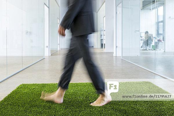 Ein reifer Geschäftsmann  der barfuß auf einem Grasteppich im Büro läuft.