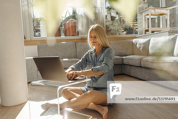 Woman at home in living room using laptop