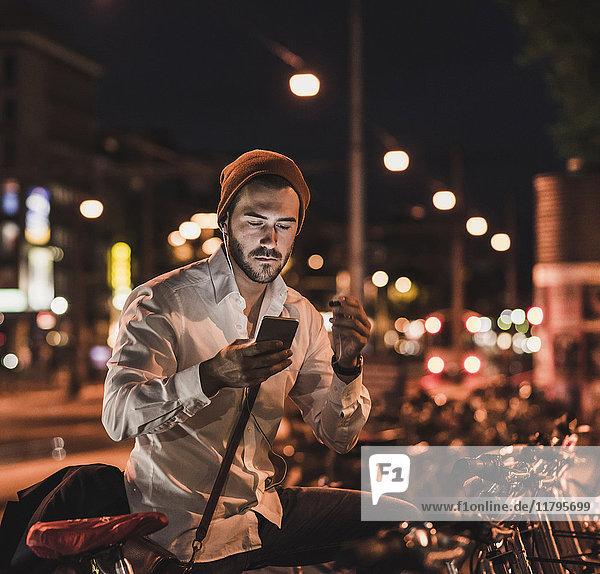Junger Mann in der Stadt  der nachts sein Handy überprüft.