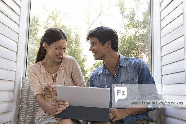 Lächelndes junges Paar sitzt auf der Fensterbank und teilt sich die Tafel.