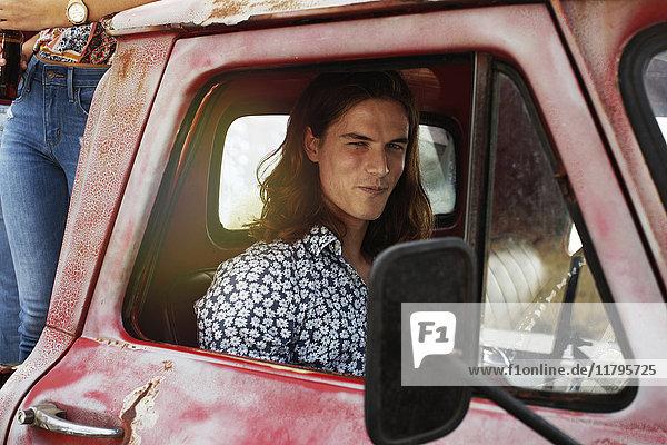 Porträt eines jungen Mannes in einem alten Pick-Up