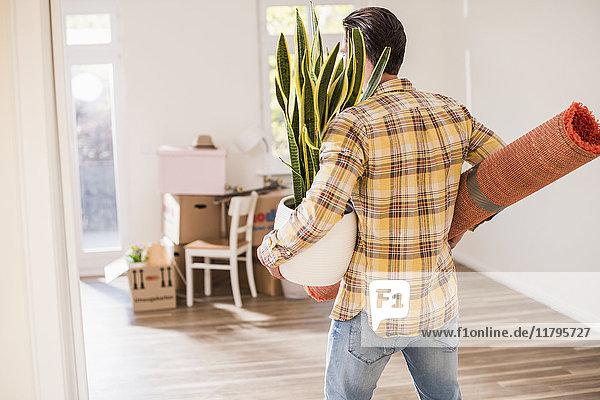 Junger Mann mit Habseligkeiten im neuen Zuhause