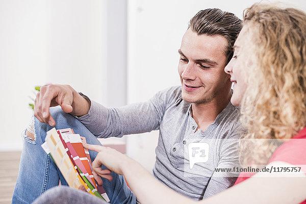Junges Paar in neuem Zuhause aus Farbmuster auswählen