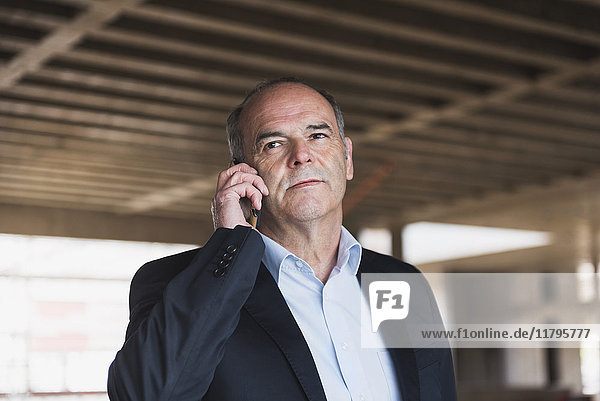 Businessman on cell phone in building under construction