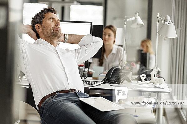 Geschäftsmann entspannt am Schreibtisch im Büro