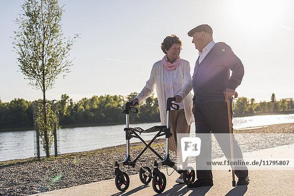 Glückliches Seniorenpaar beim Spaziergang am Fluss