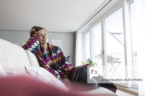 Lächelnde Frau entspannt auf der Couch