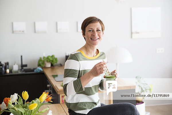 Porträt einer lächelnden Frau mit grünem Smoothie in der Küche