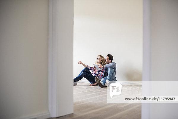 Junges Paar in neuem Zuhause sitzend auf dem Boden mit Tablette