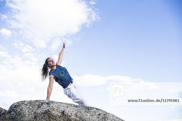 Frau bei einer Yoga-Übung auf einem Felsen