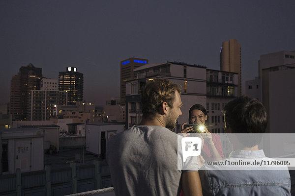 Junge Frau fotografiert Freunde auf einer Dachparty