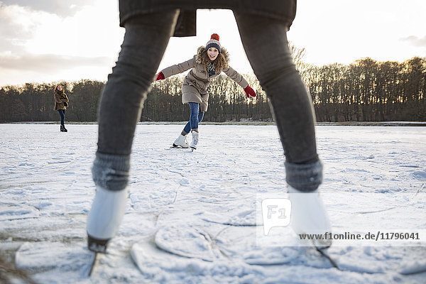Frau beim Eislaufen auf dem zugefrorenen See mit Freunden