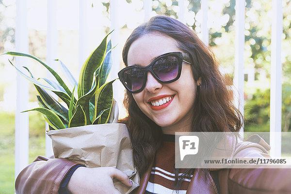 Porträt einer lächelnden jungen Frau mit Topfpflanze  die sich selbst mit dem Smartphone fotografiert.
