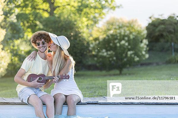 Junges Paar entspannt am Poolrand