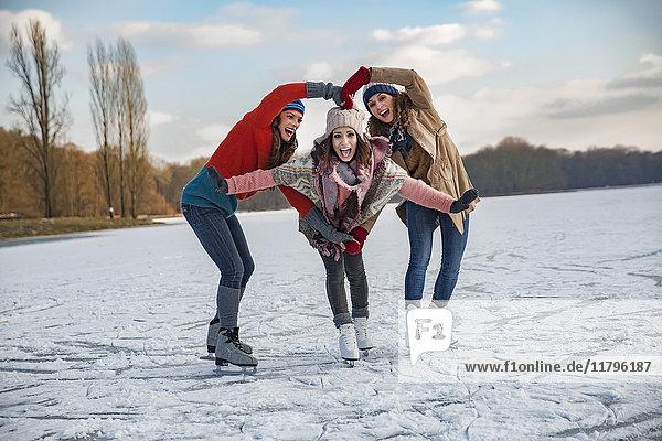 Drei Freundinnen beim Schlittschuhlaufen und mit den Armen ein Herz formend