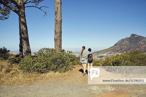 Südafrika  Kapstadt  Signal Hill  zwei junge Frauen mit Blick auf die Stadt