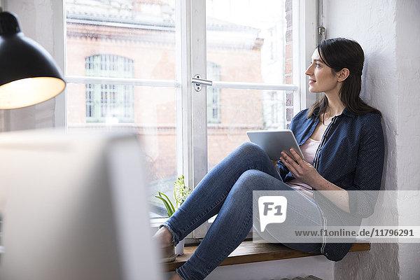 Frau mit Tablette im Büro aus dem Fenster schauend