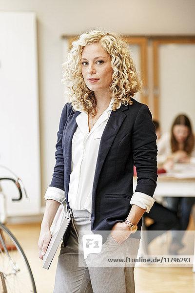 Porträt einer selbstbewussten Geschäftsfrau mit einer Besprechung im Hintergrund