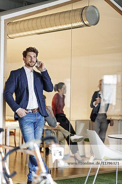 Geschäftsmann am Handy im Büro mit einer Besprechung im Hintergrund