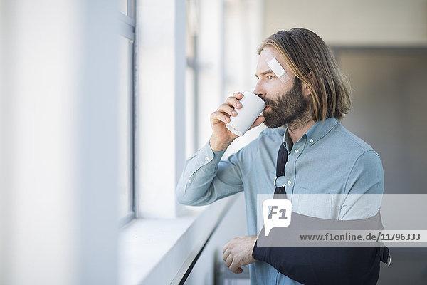 Mitarbeiter mit Schleuder beim Kaffeetrinken am Fenster