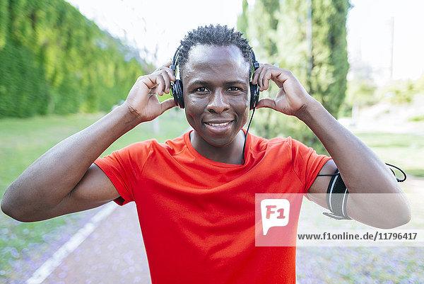Porträt eines Mannes in Sportbekleidung  der mit Kopfhörern Musik hört.