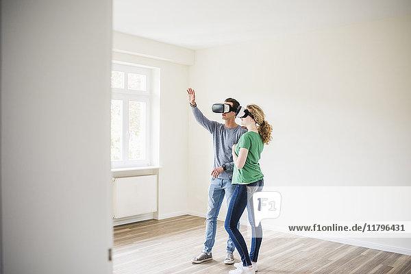 Junges Paar in leerer Wohnung mit VR-Brille