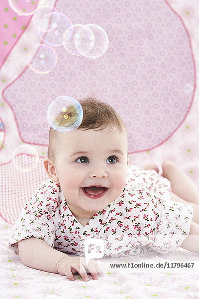 Portrait of amazed baby girl watching soap bubbles