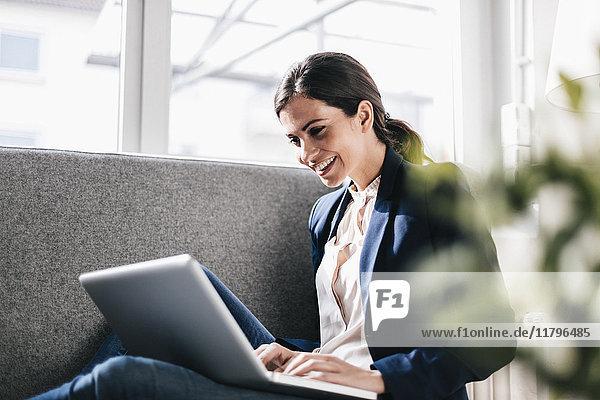 Lächelnde Geschäftsfrau mit Laptop auf der Couch
