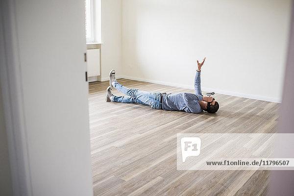Mann auf dem Boden liegend in leerer Wohnung mit VR-Brille