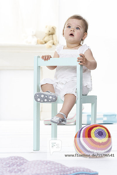Portrait of baby girl sitting on chair looking up