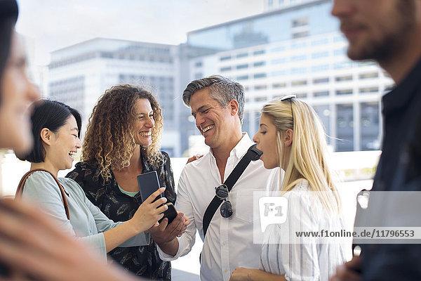 Gruppe von glücklichen Geschäftsleuten  die sich ein Handy auf dem Stadtplatz teilen.