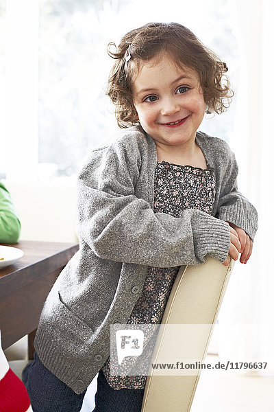 Portrait of smiling little girl kneeling on a chair at home