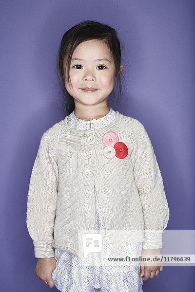 Portrait of smiling little girl wearing cardigan