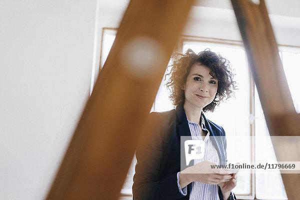 Geschäftsfrau steht an der Leiter im Büro und hält ein Smartphone.