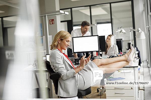 Geschäftsfrau am Schreibtisch im Büro mit Handy