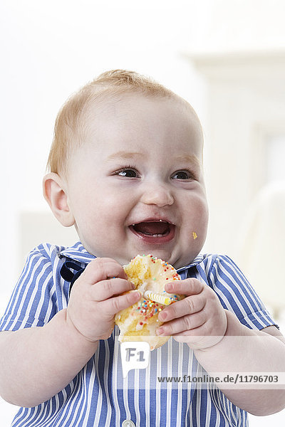 Portrait of happy baby boy with muffin
