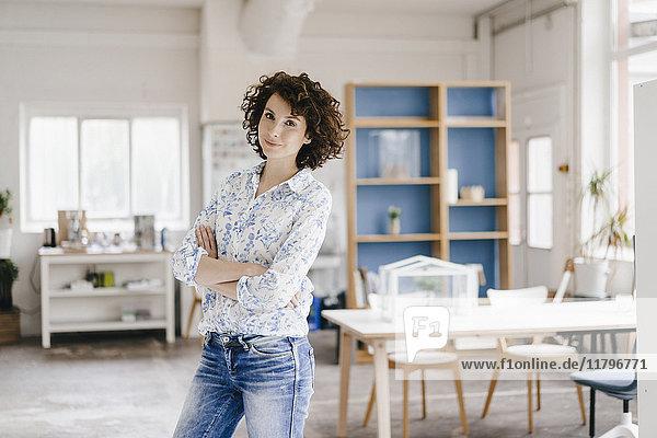 Geschäftsfrau im Büro sieht zuversichtlich aus