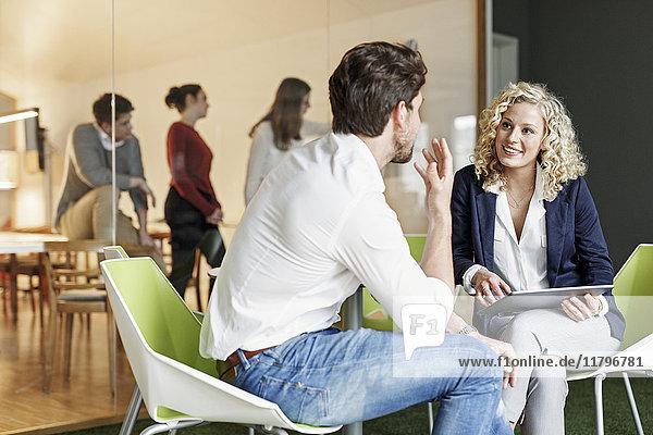 Zwei Kollegen im Büro mit Besprechung im Hintergrund