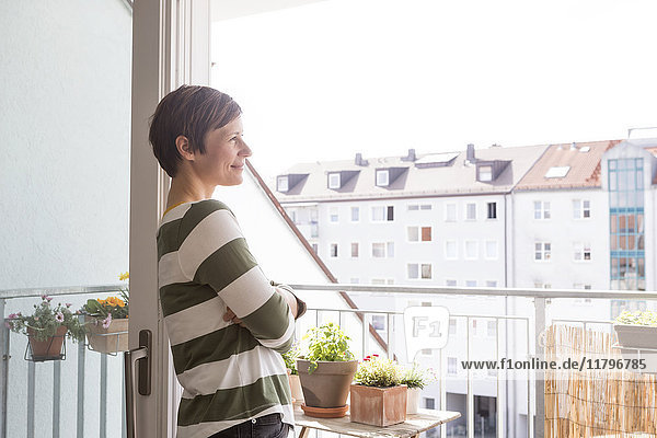Lächelnde Frau steht auf dem Balkon und schaut in die Ferne.